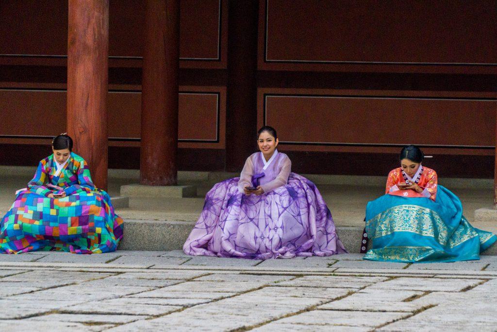 korea, do kroju oblecene zeny textuji na mobilu